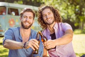 Hipster friends toasting with beers