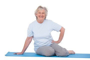 Senior woman smiling on exercise mat