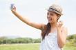 canvas print picture - Pretty brunette taking a selfie in park