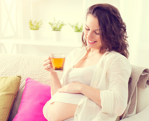 Pregnant  woman sitting on a sofa and drinking herbal tea
