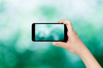 female teen hand taking picture with smart phone of green