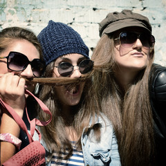 Girls having fun together outdoors and making moustache of hair,