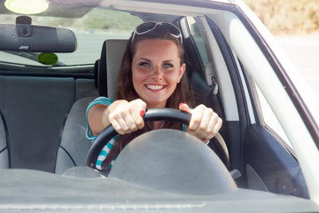Happy woman is driving a car