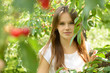 Portrait of pretty cheerful teen girl in cherry garden