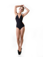 Sexy young woman posing in a black swimsuit full length isolated