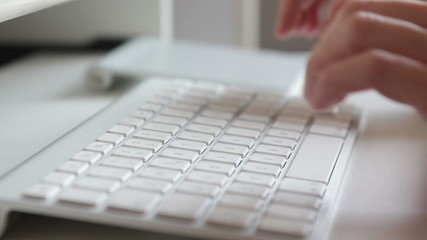 Woman hands typing on a keyboard in office setting