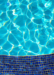 Blue tiles in the Swimming pool and sunlight reflection