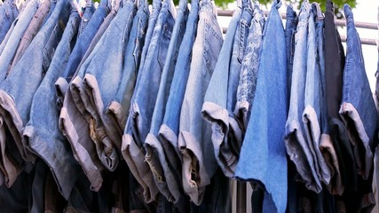 Close up of many blue jeans hanging on a rail. Video macro shift