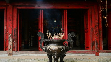 Incense Sticks Burning in Giant Pot in Front of Buddhist Temple