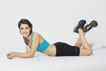 Sporty woman lying in studio