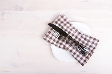 fork and knife on a plate with a napkin on wooden background