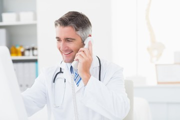 Male doctor using landline phone