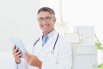 Confident male doctor using tablet computer