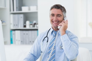 Confident male doctor using telephone in clinic