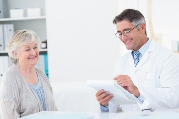 Doctor writing prescriptions for senior patient