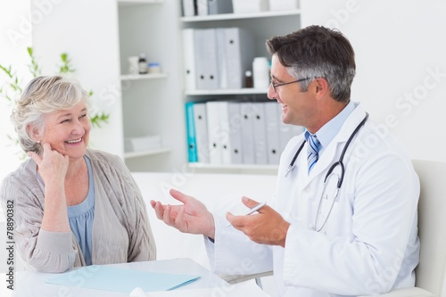 Doctor discussing with senior patient at table - 78890382