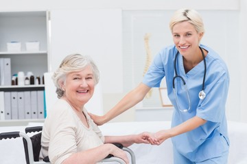 Friendly nurse holding senior patients hand
