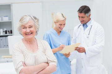 Patient smiling while doctor and nurse discussing in clinic
