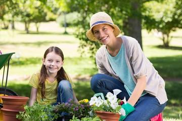 Happy blonde and her daughter gardening