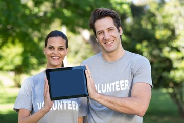Happy volunteer couple holding tablet pc