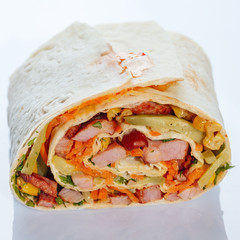 Roll of roast meat with corn and vegetables in a pita.