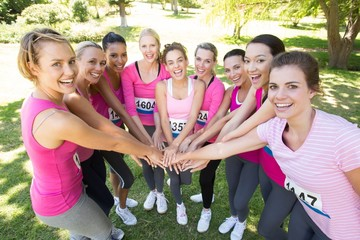 Smiling women running for breast cancer awareness