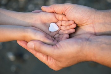 Close up of child and man hands with heart