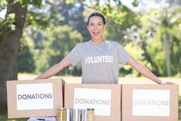 Pretty volunteer with donation boxes in park