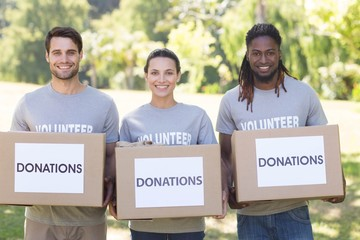 Happy volunteers with donation boxes in park