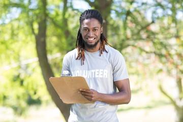 Happy volunteer in the park holding clipboard