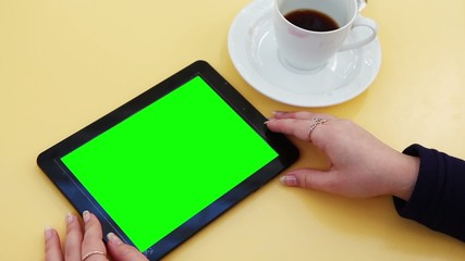 woman holds a blank tablet PC with a green screen
