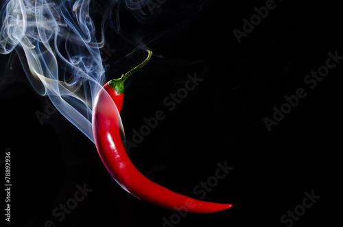 Fototapeta Smoking red hot chili pepper on black background