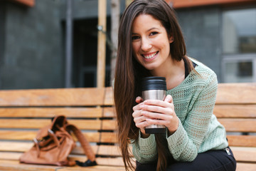 Young beautiful woman drinking coffee in outdoors.