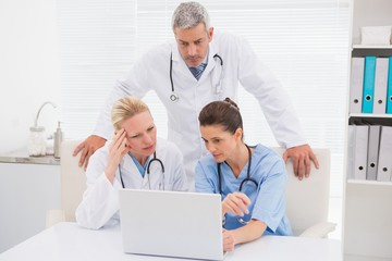 Doctors looking at laptop