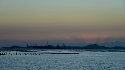 Time lapse of sunset at sea with shipping cargo port background