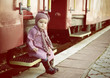 Little cute girl ready to vacation on railway station, baby girl