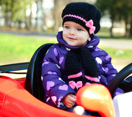 Happy cute little girl in park driving a car