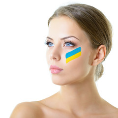 Portrait of attractive girl with ukrainian flag on her face, ove