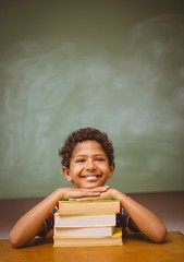 Little boy with stack of books in classroom