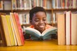 Cute boy reading book in library - 78895383