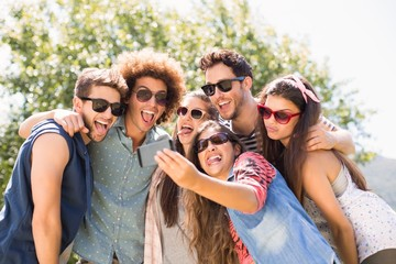Happy friends in the park taking selfie