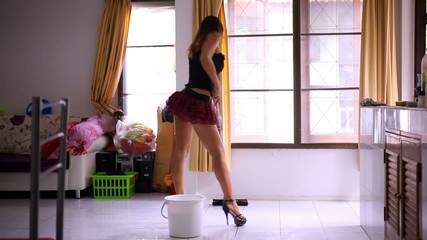 Beautiful young sexy maid cleans tiled floor, concept cleaning