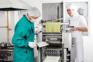 Chefs Preparing Ravioli Pasta In Machine