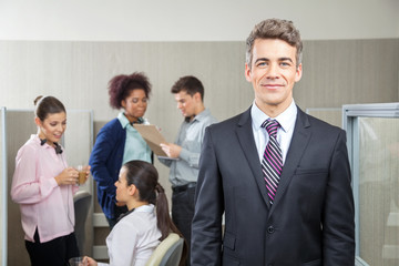 Confident Manager With Employees Discussing In Background