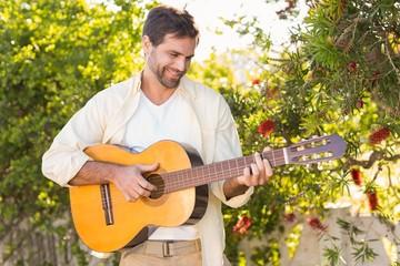 Happy man smiling at camera playing guitar