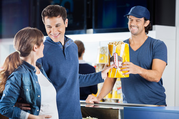 Expectant Couple Buying Popcorn At Concession Stand