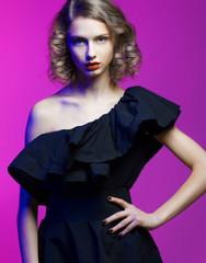Fashion Beauty Girl Portrait on pink Background in black dress.