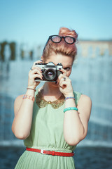 Beautiful girl in vintage clothing making picture with retro cam