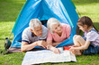 Grandparents With Granddaughter Discussing Over Map At Campsite