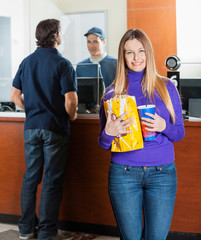 Beautiful Woman Holding Snacks While Man Buying Movie Tickets